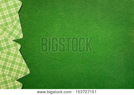 Background with cards on green felt casino table. Copy space on felt field
