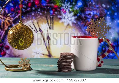 Christmas theme with toy ball cookies and mug on green wooden surface against nice clock background.