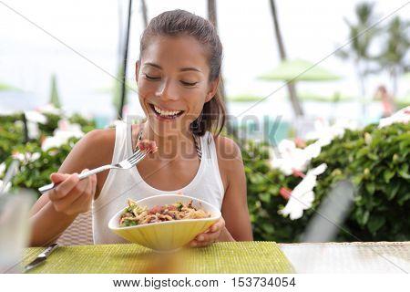Asian woman eating a fresh raw tuna dish, hawaiian local food poke bowl, at outdoor restaurant table during summer travel vacation. Hawaii poke bowl food plate. Ahi tuna hawaiian cuisine.
