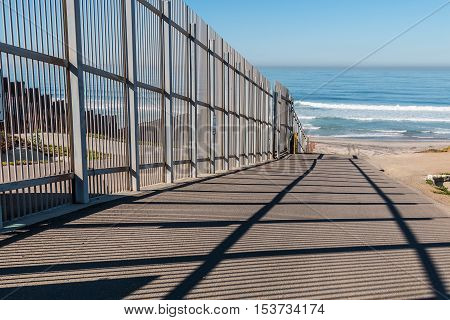 Inner fence of the international border wall which extends out into the Pacific ocean and separating San Diego, California from Tijuana, Mexico.