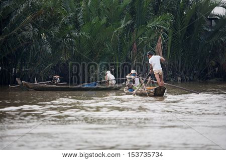 Mekong River, Vietnam-October 24, 2009. People in small wooden boats move along the Mekong River Delta, Vietnam