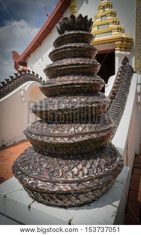 the copper tail end of Naga stand on the long cemet stair in front of temple.
