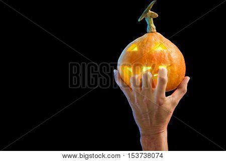 Hand hold pumpkin head jack halloween isolated on black