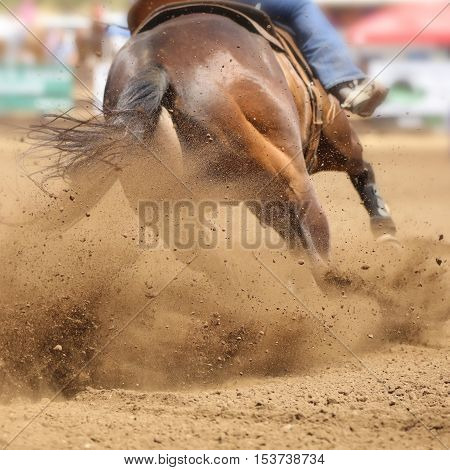 A galloping horse sliding and kicking up dirt at a rodeo competition.