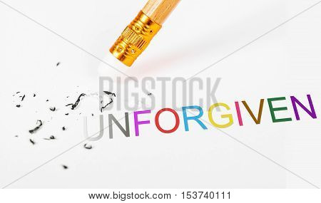 Changing the word unforgiven to forgiven with a pencil eraser on white paper. Concept of Forgiven Mercy Repentance Reconcile Change.