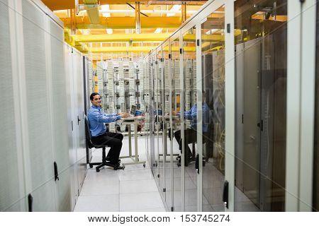 Technician working on laptop in server room
