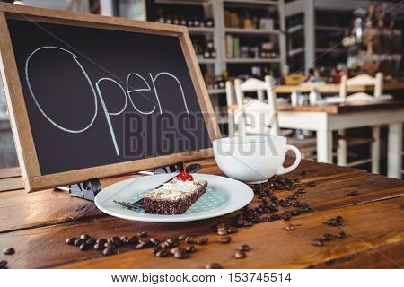 Open signboard with slice of cake and coffee cup on a table in cafeteria