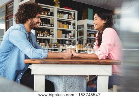 Couple holding hands and smiling in cafeteria