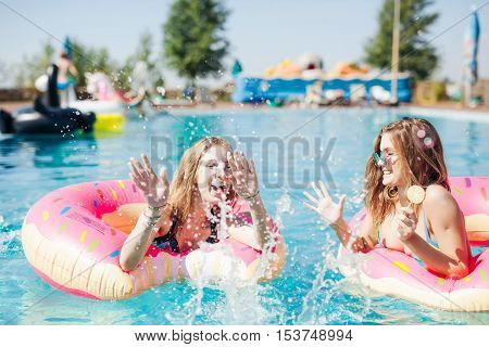 Two girls playing with water in the pool mattresses donuts 20s