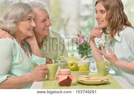 Cute family portrait , adult daughter with senior parents drinking tea