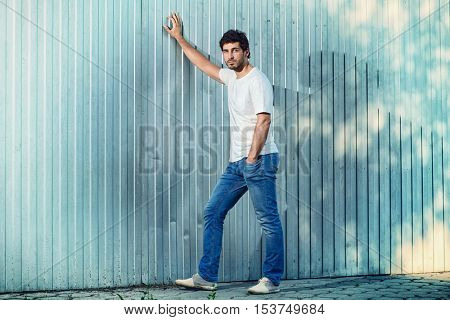 Full length portrait of a calm handsome young man leaning to the wall outdoor.