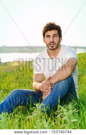 Handsome young man standing on a green lawn over urban background.