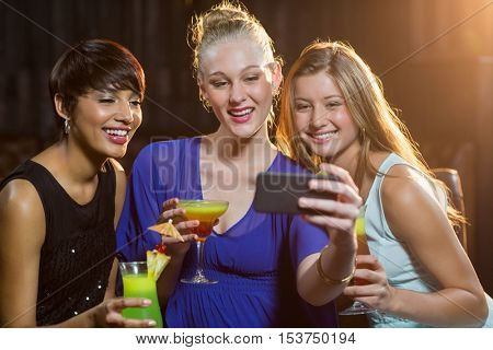 Smiling female friends taking a selfie from mobile phone while having cocktail in bar