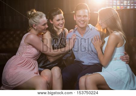 Smiling friends sitting together in sofa at bar