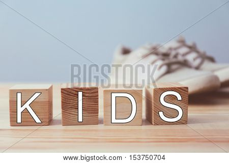 Word KIDS made of wooden cubes and boots on wall background