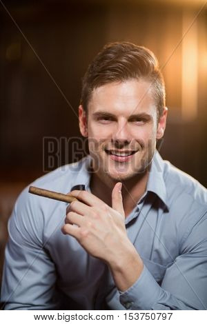 Portrait of smiling man holding a cigar in bar