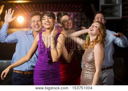 Group of smiling friends dancing on dance floor in bar