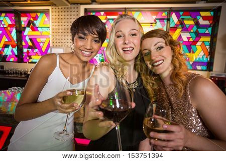 Portrait of three smiling friend having glass of champagne at bar