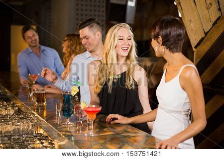 Group of smiling friends interacting with each other at bar counter while having cocktail in bar