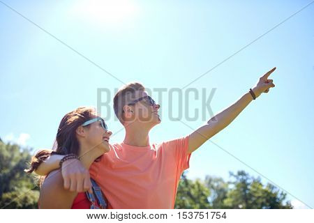 holidays, vacation, love and people concept - happy smiling teenage couple hugging and pointing finger up to something at summer