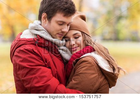 love, relationships, season and people concept - close up of happy young couple hugging in autumn park