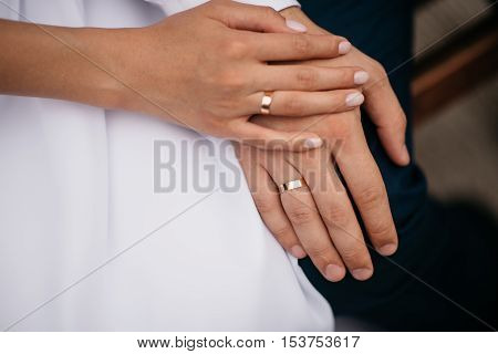 Newly wed couple's hands with gold wedding rings
