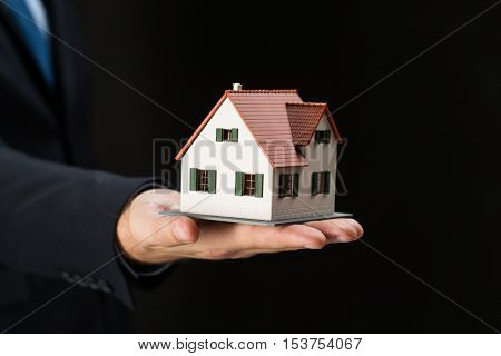 architecture, building, construction, real estate and property concept - close up of businessman or real estate agent hand holding house or home model over black background