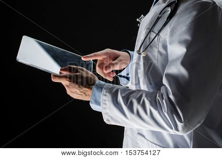 healthcare, people, technology and medicine concept - close up of male doctor in white coat with stethoscope and tablet pc computer over black background