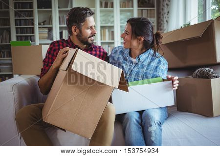 Couple talking on the sofa while unpacking cartons in the new house