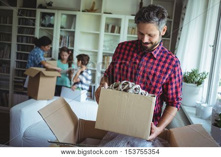 Smiling man holding a cartons in their new house and family standing behind him