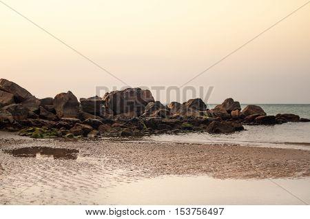 Rugged coastline and tide on the beach at sunrise