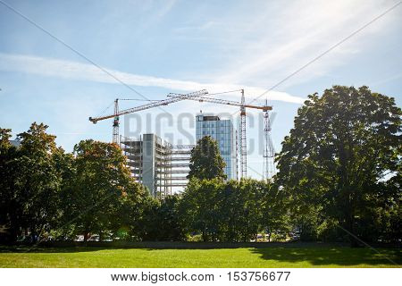 building, architecture, industry and engineering concept - crane at construction site building living house