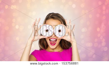 people, holidays, junk food and fast food concept - happy young woman or teen girl in pink dress having fun and looking through donuts over rose quartz and serenity lights background