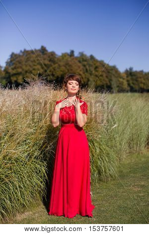 Girl in evening red dress in a warm summer day