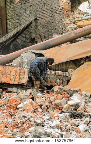 Tyumen, Russia - February 16, 2008: Demolition of machine-tool factory. Worker cutting metal with with acetylene torch