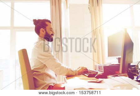 business, startup and people concept - happy businessman or creative male office worker with computer