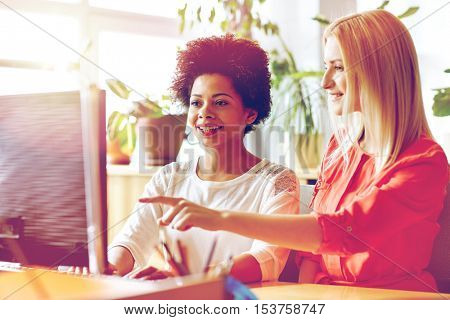 business, education, startup and people concept - happy women or students with computer in office