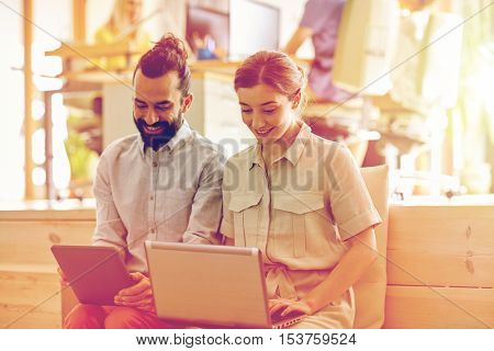 business, technology, startup and people concept - happy creative team with tablet pc and laptop computer in office
