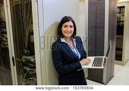 Portrait of beautiful technician working on laptop in server room