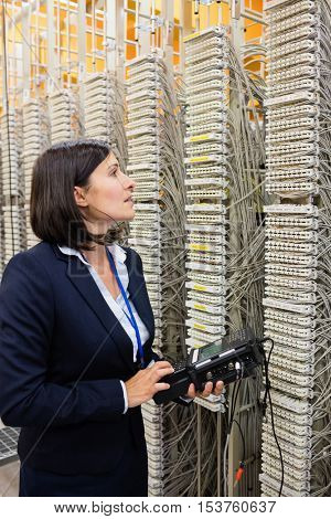 Close-Up of technician using digital cable analyzer in server room