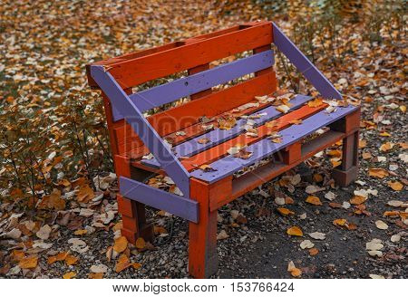 Park bench sprinkled with autumn leaves.Autumn background