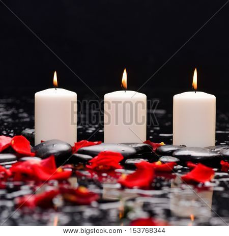 Many rose petals with three candle and therapy stones