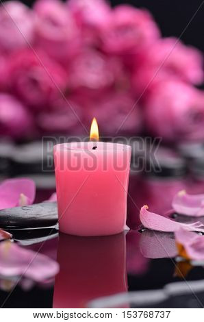 Still life with branch rose with pink candle and therapy stones