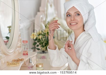 Young attractive woman near mirror in bathrobe