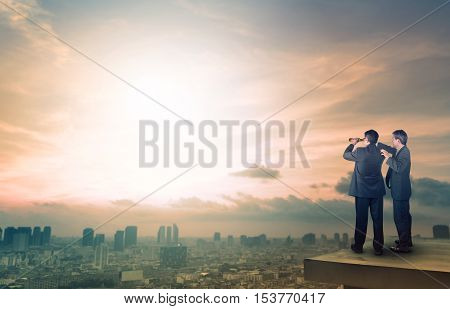 two business man and binocular spying acting standing on top of office building and watching lens to target