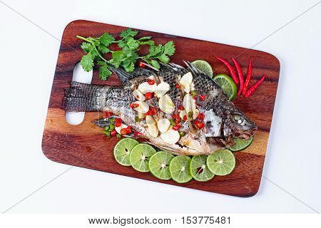 Tilapia fish streamed with lemon topped spicy sour ginger and chili on butcher served. (Call Pla Nil Nuang Manoaw in Thai) isolated white background.