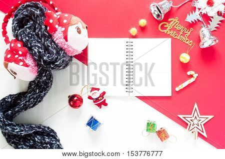Flat lay of Christmas Decoration gift boxes and empty notebook top view on white and red background