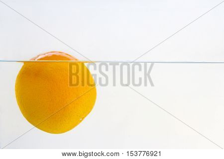 A orange floating in a water close up and isolated