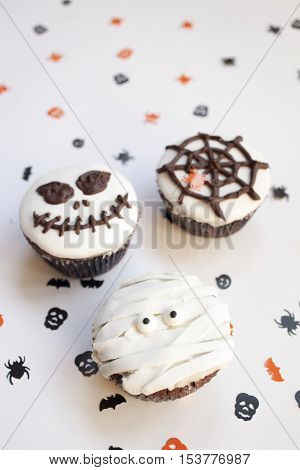 Home made Halloween spooky and creepy muffin cupcakes as a mummies, spider net and horror pumpkin, decorated with chocolate to Halloween party, on bright white background, selective focus