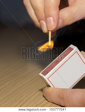 Close up of female hands lighting a match on box with flame
